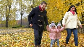 Parents with children playing in the park with yellow leaves in
