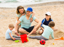 Parents with  children playing in the sand Royalty Free Stock Images