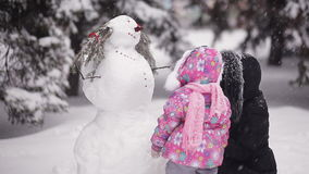 Parents and children playing in the snow. Mom and daughter sculpt of snow in the winter woods. stock footage
