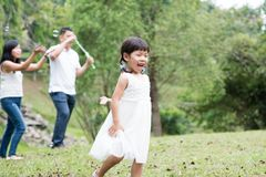Asian family blowing soap bubbles. Parents and children playing soap bubbles at park. Asian family outdoors activity royalty free stock photography