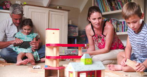 Parents And Children Playing With Toys In Bedroom. Mother and son play with wooden train set in child's bedroom whilst father and daughter have fun with digital stock video footage