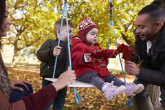 Parents With Children Playing On Tree Swing In Autumn Garden Royalty Free Stock Images