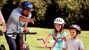 Parents and children pointing the way to go while they are riding bicycle stock footage