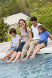 Parents and children putting feet in swimming pool Stock Images