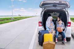 Parents with children ready for a road trip. Young parents with their children ready for a road trip while sitting together in the car trunk. Shot on the highway Royalty Free Stock Images