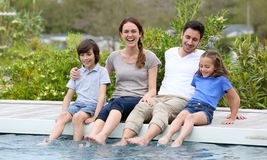 Parents and children relaxing by pool Royalty Free Stock Photo