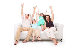 Parents and children with rised hands on sofa stock photo