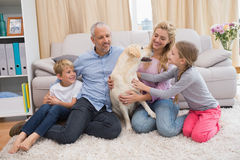 Parents and children on rug with labrador Royalty Free Stock Photos