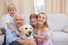 Parents and children on rug with labrador Stock Images