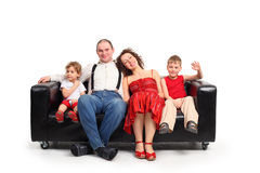 Parents with children sit on black leather sofa Royalty Free Stock Photos