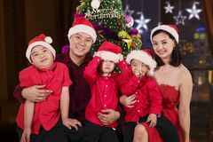 Parents with children sitting near a Christmas tree. Picture of happy parents with their sons sitting near a Christmas tree at home stock images