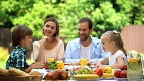 Parents and children sitting at table, enjoying family dinner, having fun, joy stock image