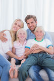 Parents and children sitting together on couch Stock Photos