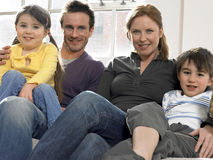 Parents And Children Smiling At Home Stock Photography
