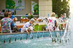 Parents with children splashing in the fountain. Stock Image