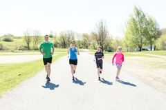 Parents with children sport running together outside. The Parents with children sport running together outside stock photo