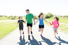 Parents with children sport running together outside. The Parents with children sport running together outside royalty free stock image