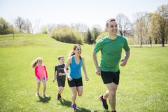 Parents with children sport running together outside. The Parents with children sport running together outside royalty free stock images