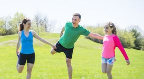 Parents with children sstretching together outside. The Parents with children sport stretching together outside stock photography