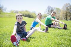 Parents with children sstretching together outside. The Parents with children sport stretching together outside stock photo