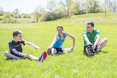 Parents with children sstretching together outside. The Parents with children sport stretching together outside royalty free stock photo