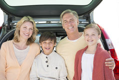 Parents And Children Standing In Front Of Open Car Trunk Stock Photo
