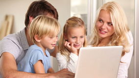Parents and children talking and using a laptop Royalty Free Stock Images