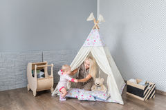 Parents with children in a teepee. Parents play with children in a teepee tent in the bright nursery Royalty Free Stock Images