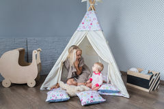 Parents with children in a teepee stock images