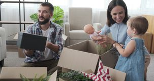 Family unpacking carton box in new house stock footage