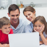 Parents and children using a laptop. In the kitchen stock image