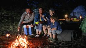 Parents with childs broil marshmallow on campfire to woodland, happy family fry marshmallow at fire. In travel camp in forest, mom and daddy with kids resting