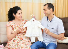 Parents choose clothes for the newborn baby. pregnant woman and man. happy couple sitting on the couch at home Stock Images
