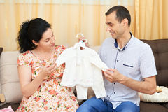 Parents choose clothes for the newborn baby. pregnant woman and man. happy couple sitting on the couch at home Royalty Free Stock Photo