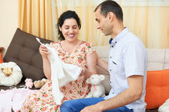 Parents choose clothes for the newborn baby. pregnant woman and man. happy couple sitting on the couch at home Stock Image
