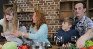 Parents cocinar con los niños en cocina en casa, familia feliz pasan el tiempo junto mientras que prepara la comida almacen de metraje de vídeo