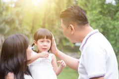 Parents comfort crying daughter outdoors. Parents comfort crying daughter at outdoor garden park. Asian family outdoors portrait royalty free stock photo