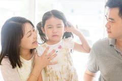 Parents comforting crying child at home. Parents comforting crying child. Asian family at home, natural living lifestyle indoors Stock Photos
