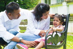 Parents is comforting their crying daughter. Indian family outdoor. Parents is comforting their crying daughter Stock Images