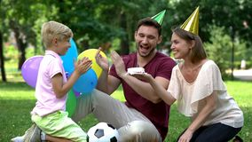 Parents congratulating son with birthday, party outside, unexpected surprise stock photos