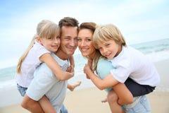 Parents crianças levando em suas partes traseiras na praia fotos de stock