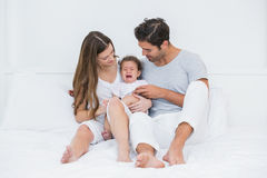 Parents with crying baby sitting on bed. At home Royalty Free Stock Photo