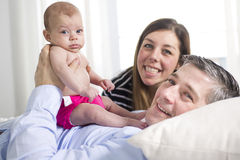 Parents Cuddling Newborn Baby In Bed At Home Stock Photo