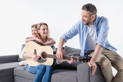 Parents with cute little daughter sitting together on sofa and playing guitar Royalty Free Stock Image