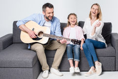 Parents with cute little daughter sitting together on sofa and playing guitar Stock Images