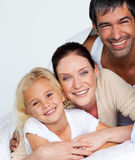 Parents and daughter on bed smiling at the camera Stock Photos