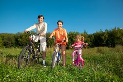 Parents with daughter on bicycles in park, day. Stock Photo