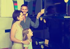 Parents with daughter choosing new big TV screen in home applian Stock Photos