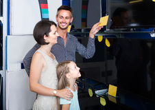parents with daughter choosing new big TV screen in home appliance store stock photo