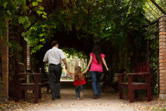 Parents with daughter enter into tunnel from ivy. Parents together with daughter enter into tunnel from an ivy in summer garden Royalty Free Stock Photo
